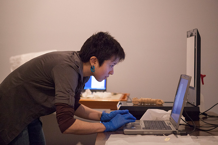 Museum intern scanning and cataloging object into collection database