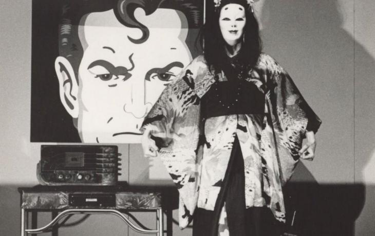 Black and white image with a cartoon depiction of Superman in the background. In the foreground an actor wears a mask and a kimono and listens to an old-fashioned radio.