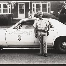 "<a href=""https://spencerartapps.ku.edu/collection-search#/object/54772"" target=""_blank""><i>untitled (police officer with squad car)</i> by Thaddeus Holownia</a>"