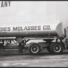"<a href=""https://spencerartapps.ku.edu/collection-search#/object/54830"" target=""_blank""><i>untitled (trucker posing with molasses tanker truck)</i> by Thaddeus Holownia</a>"