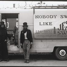 "<a href=""https://spencerartapps.ku.edu/collection-search#/object/54836"" target=""_blank""><i>untitled (two chimney sweepers in front of a truck)</i> by Thaddeus Holownia</a>"