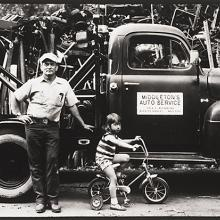 "<a href=""https://spencerartapps.ku.edu/collection-search#/object/54841"" target=""_blank""><i>untitled (man and child in front of a tow truck)</i> by Thaddeus Holownia</a>"