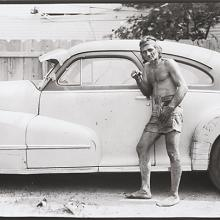 "<a href=""https://spencerartapps.ku.edu/collection-search#/object/54872"" target=""_blank""><i>untitled (a man smoking posed with a car)</i> by Thaddeus Holownia</a>"