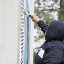 Artist Alexandra Bell applies wheat paste to her artwork <i>A Teenager with Promise, Annotated</i> to affix this piece to the east wall of Watson Library.